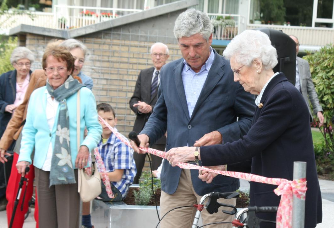 Mevrouw De Jong, langst wonende bewoonster van Eeckenrhode, verricht onder toeziend oog van burgemeester Henri de Wijkerslooth de officiële openingshandeling.